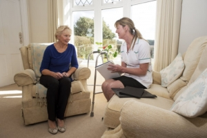caregiver on a home visit talking to an elderly female patient