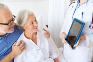 doctor showing a tablet pc to and old couple